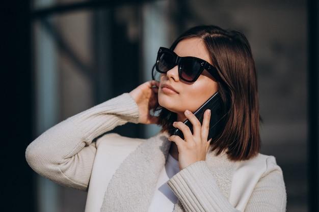 Портрет молодой женщины в городе с помощью телефона