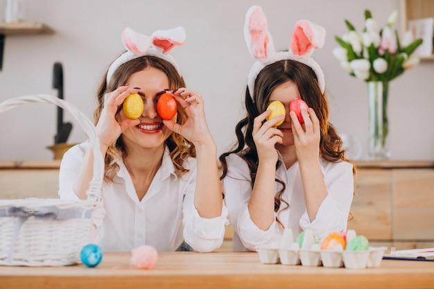 イースターの卵を塗る娘を持つ母