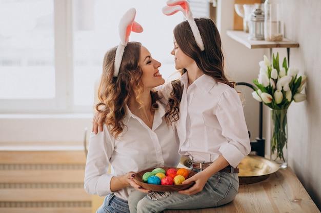 Мать с дочерью красит яйца на пасху