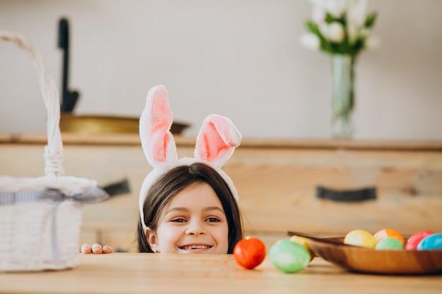 Маленькая девочка красит яйца на пасху