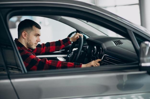 若い男が車のショールームで車を選ぶ