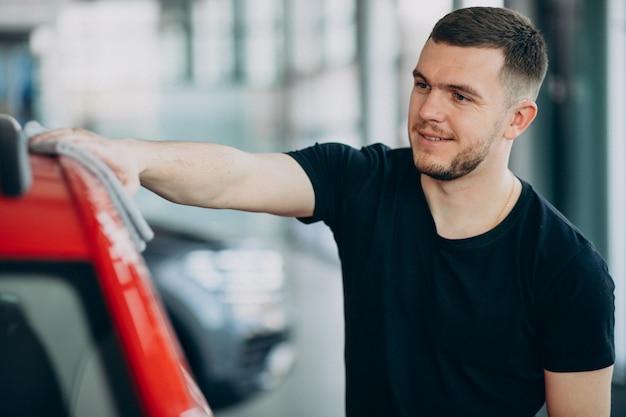 若い男が布で彼の車を研磨