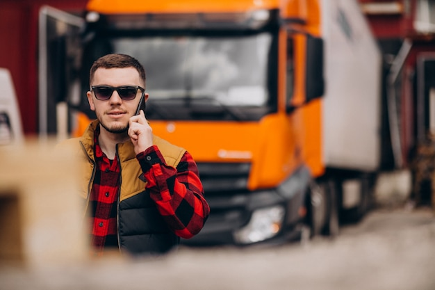 ハンサムな男のトラックの運転手がトラックのそばに立って