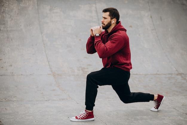 スポーツウェアの公園で運動しているハンサムな男