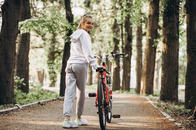 Молодая спортивная женщина езда на велосипеде в парке