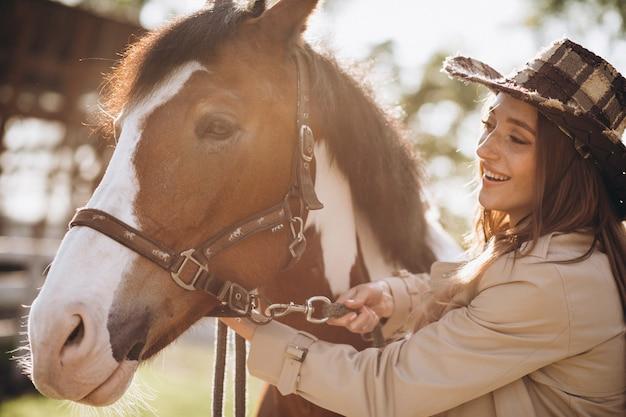 Молодая счастливая женщина с лошадью на ранчо