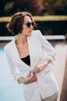 Молодая женщина в стильном белом деловом костюме
