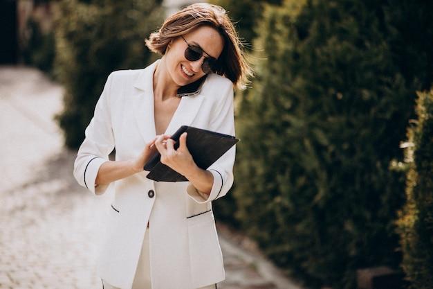屋外で電話で話している白いスーツの若いビジネス女性