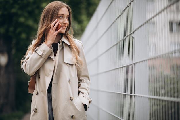 Красивая женщина с телефоном на открытом воздухе