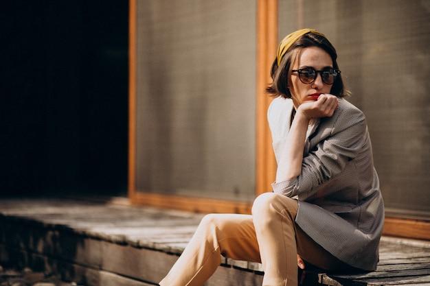 Молодая стильная женщина, сидящая на заднем дворе