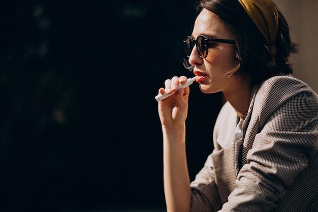 若い女性に座って、タバコを吸って