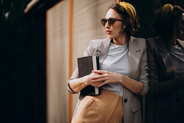 Молодая женщина, стоящая с книгой на открытом воздухе