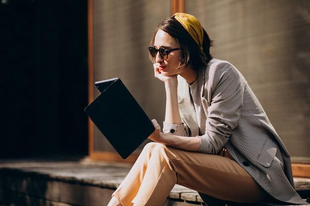 Молодая женщина сидит на заднем дворе и читает книгу