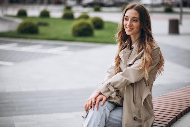 Молодая красивая женщина, сидя в парке