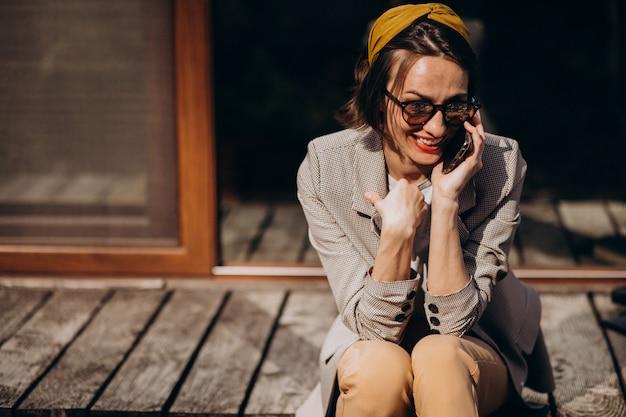 Красивая женщина, сидя на заднем дворе и с помощью телефона
