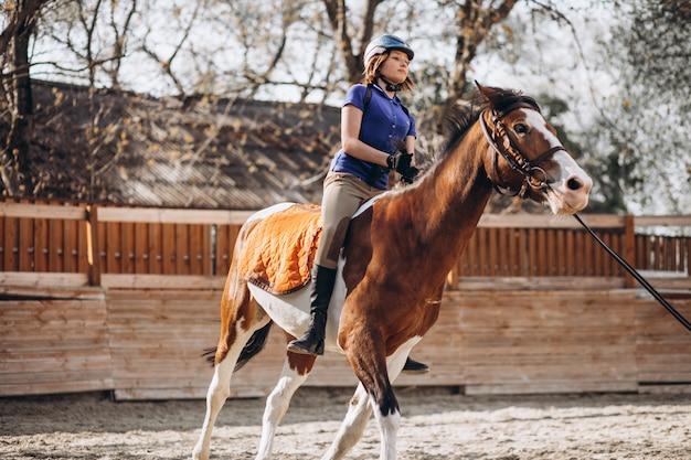 Молодая девушка учит верховой езде