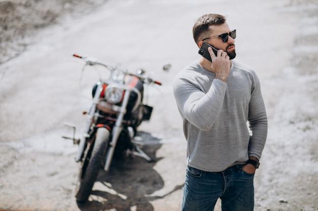 旅行バイクの若いハンサムな男