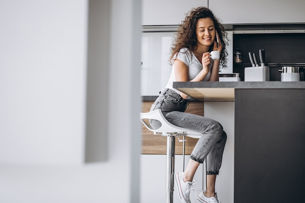 キッチンでコーヒーを飲む若い女性