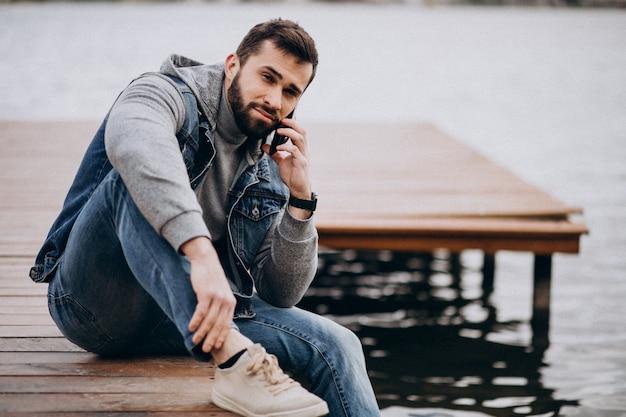 ドックに座っている公園の川で格好良いひげを生やした男