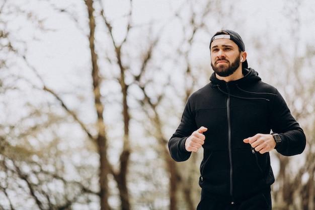 Красивый мужчина упражнения в парке в спортивной одежды