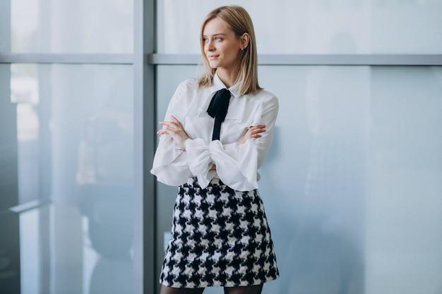 Молодая милая бизнес-леди стоя в офисе