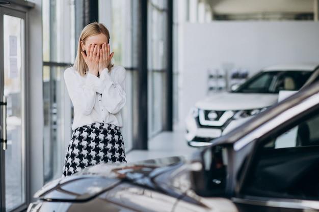 Женщина продавец в автосалоне, стоя у машины