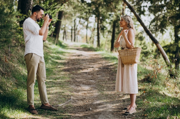 森の中の写真を作る若いカップル