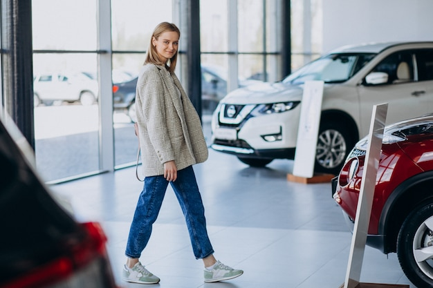 車のショールームで車を選ぶ若い女性