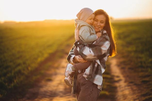 夕日に小さな娘を持つ若い母親