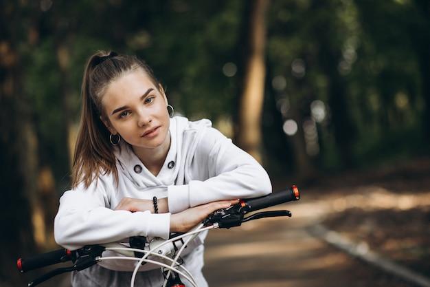 公園で若いスポーティな女性乗馬自転車