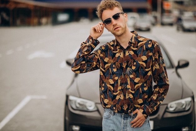 Молодой красивый мужчина стоял на машине