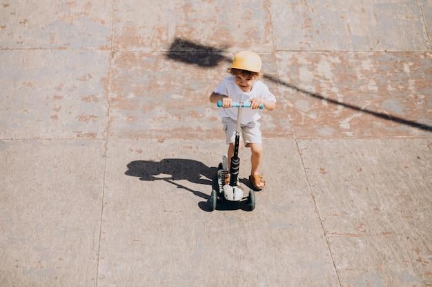 Милый маленький мальчик с вьющимися волосами езда скутер