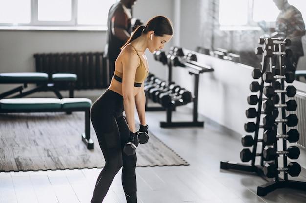 Молодая привлекательная женщина, осуществляя с гантелями в тренажерном зале