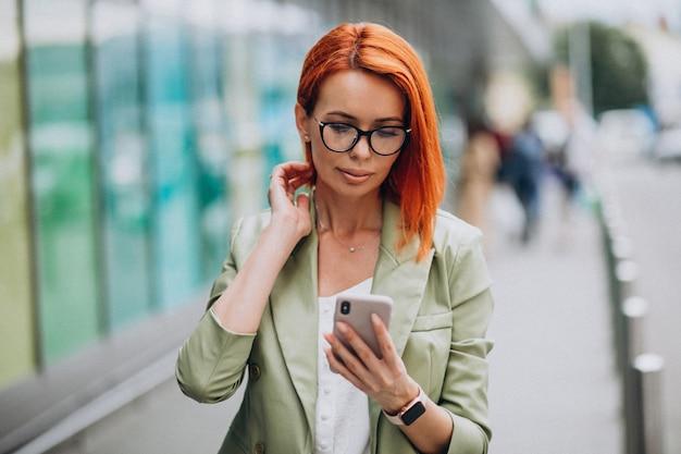 電話で話している緑のスーツの若い美しい成功した女性