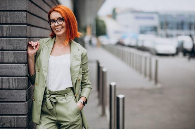 壁のそばに立っている緑のスーツのビジネスウーマン