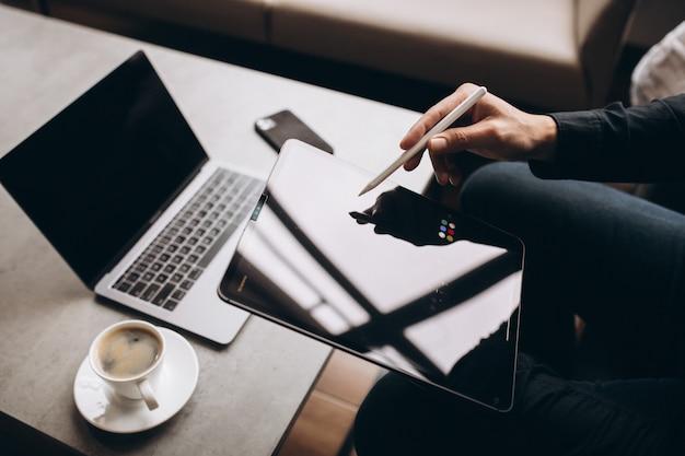 Человек, работающий на планшете за столом