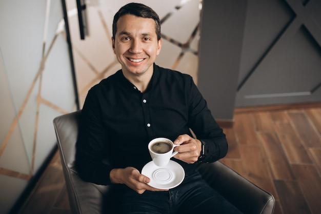ハンサムなビジネスの男性がオフィスでコーヒーを飲む