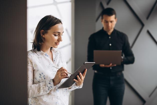 ビジネスの女性とビジネスマンの同僚のラップトップに取り組んで
