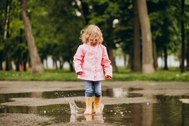 Милая маленькая девочка прыгает в лужу в дождливую погоду