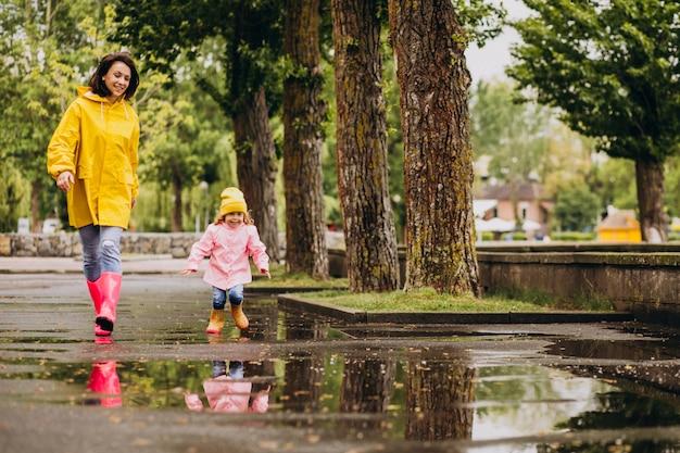 水たまりにジャンプ楽しい娘を持つ母