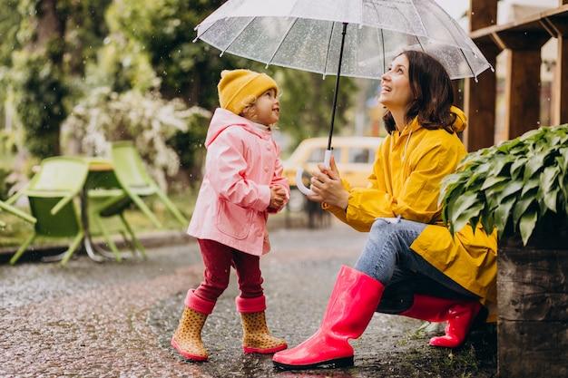 ゴム長靴を着て雨の中で公園を歩いて娘を持つ母