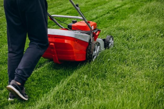 Человек косит траву газонным двигателем на заднем дворе