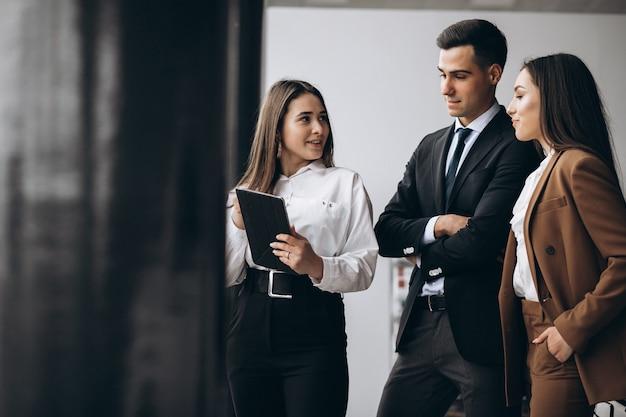 Мужские и женские деловые люди, работающие на планшете в офисе