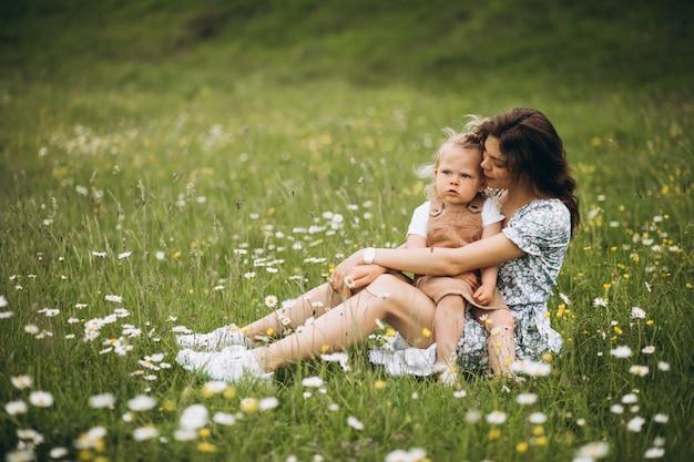 Молодая мать с маленькой дочерью в парке, сидя на траве