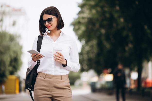 街の通りの外で電話で話している女性