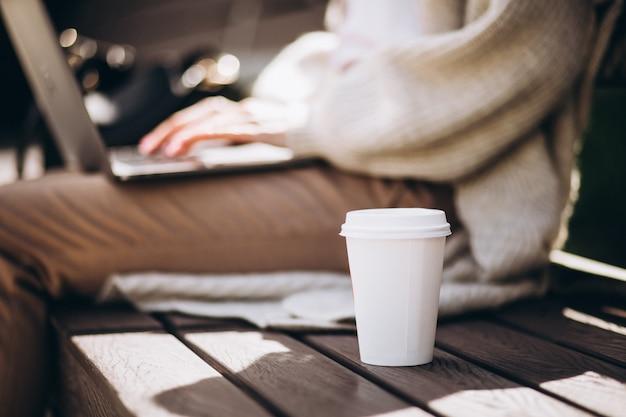 フォーカスのコーヒーカップとラップトップに入力する女性の手