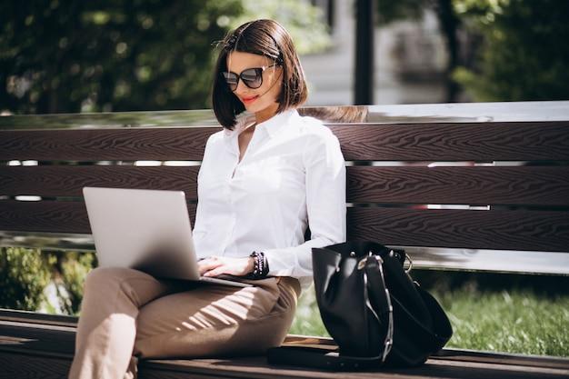 公園の外のラップトップに取り組んでいるビジネス女性