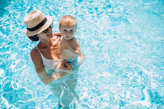 プールで楽しんでいる幼い息子を持つ母