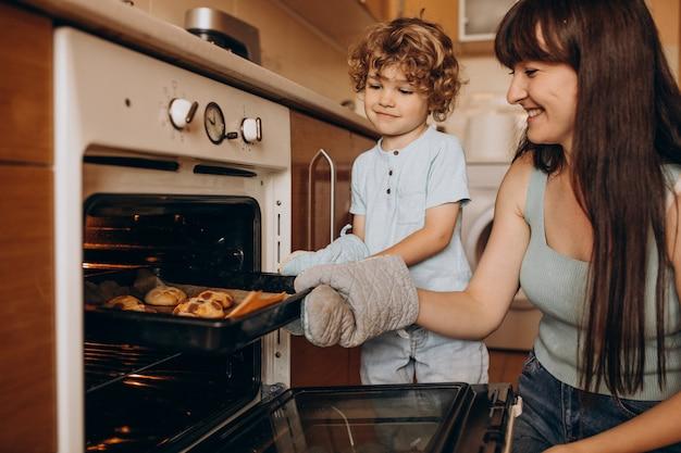 オーブンでクッキーを焼く幼い息子を持つ母