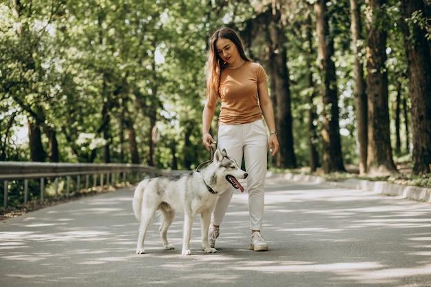 Женщина с ее хаски в парке
